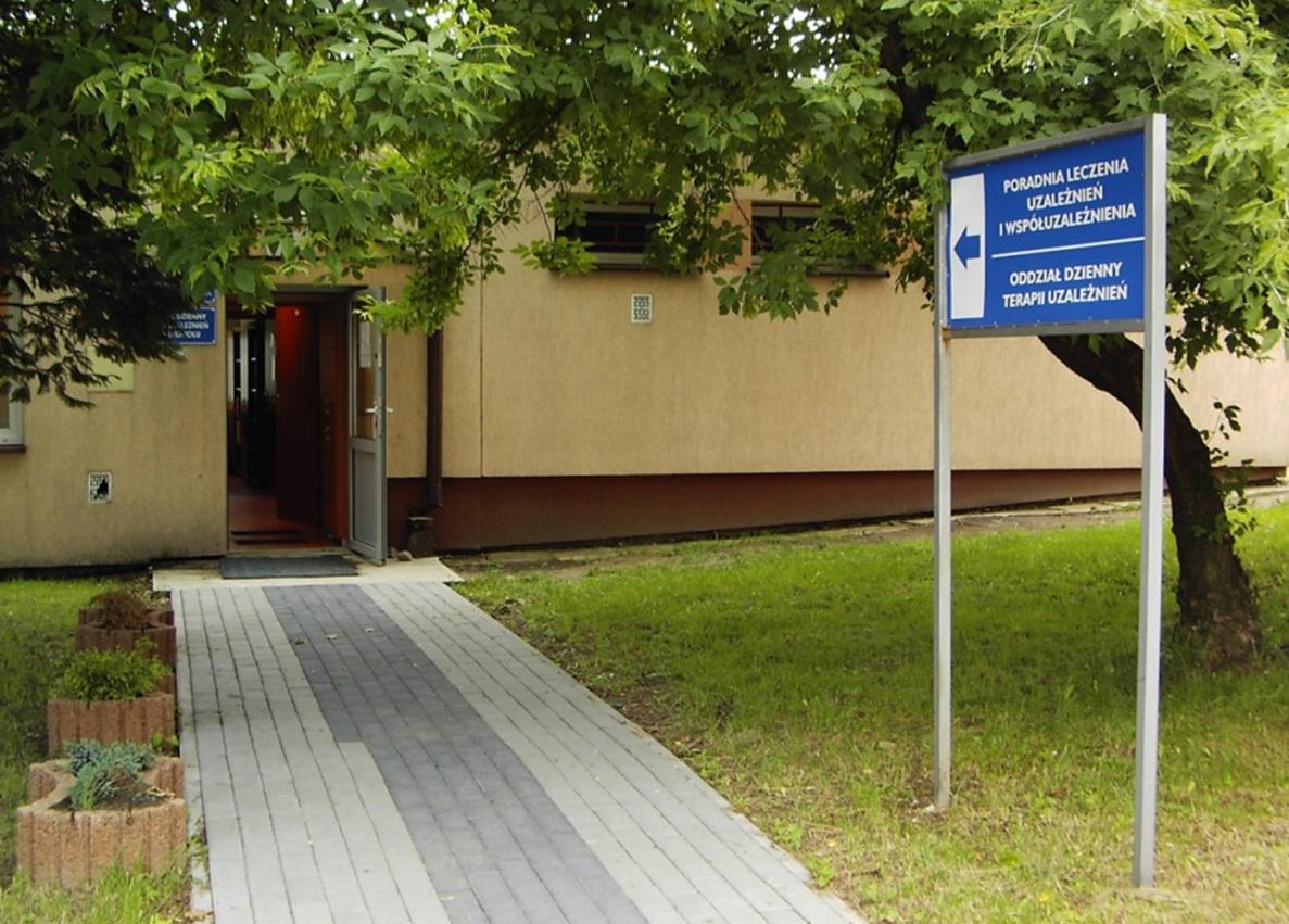 Wejście do ośrodka leczenia uzależnień z tablicą informacyjną