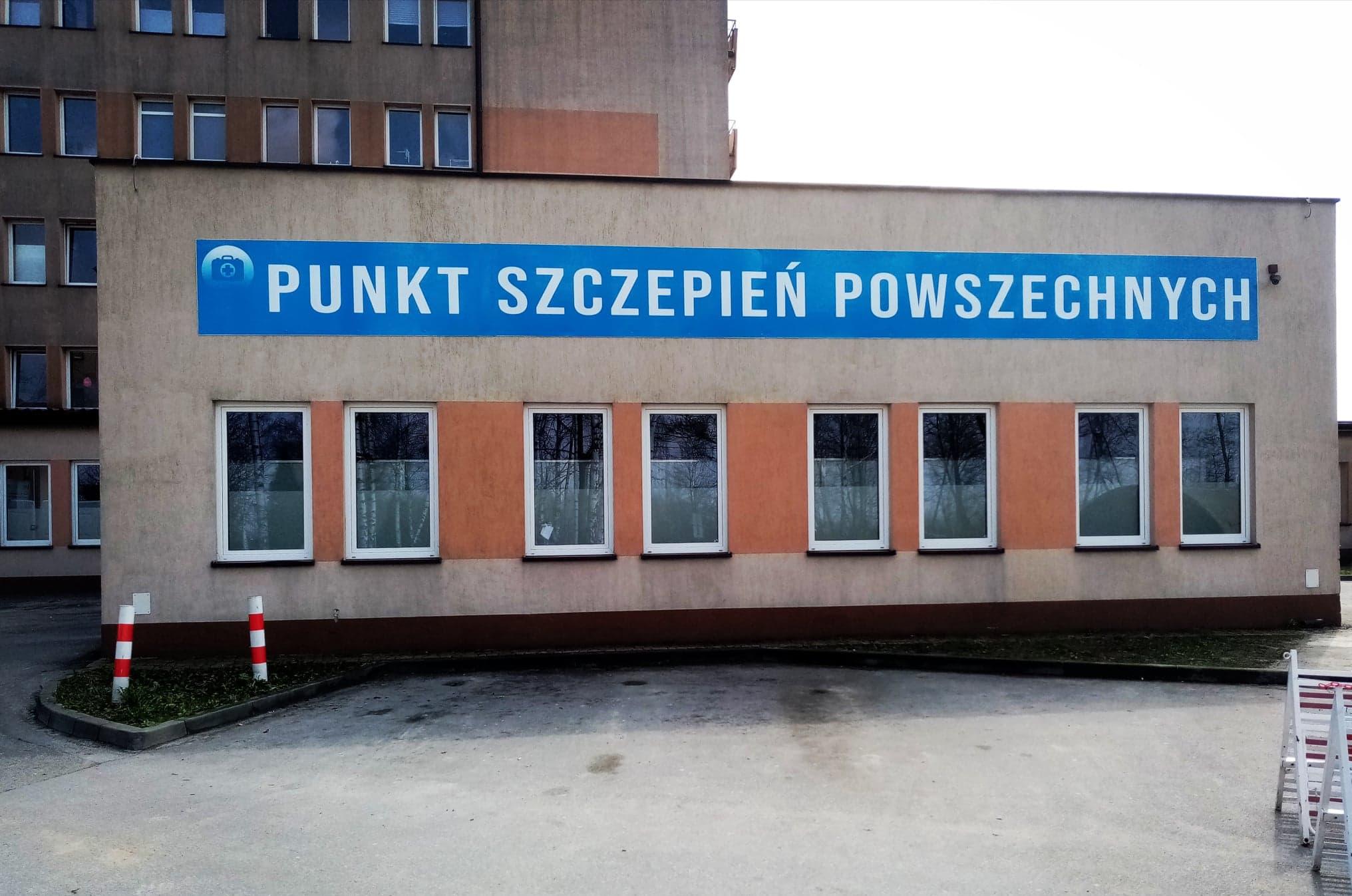 biały naps Punkt Szczepien Powszechnych na niebieskim tle na budynku gdzie znajduje się punkt szczepień